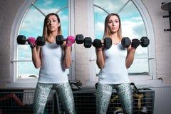 Красивые женщины фитнеса делая бицепсы работают в спортзале Стоковое Изображение RF