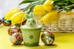 Красивые желтые тюльпаны в белых плетеной корзине и пасхальных яйцах Стоковое фото RF