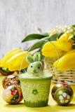 Красивые желтые тюльпаны в белых плетеной корзине и пасхальных яйцах Стоковое Изображение RF
