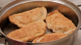 Красивые зажаренные пироги мяса сварены в лотке в горячем постном масле Конец-вверх Блюда металла сияющие сток-видео