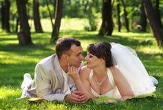 Красивые заново пожененные пары лежа на траве на парке Стоковое фото RF