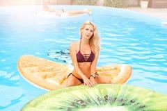 Красивые заплывы молодой женщины в бассейне на раздувной игрушке в форме части плода стоковое фото
