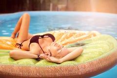Красивые заплывы молодой женщины в бассейне на раздувной игрушке в форме части плода стоковое фото rf