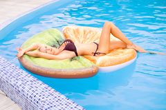 Красивые заплывы молодой женщины в бассейне на раздувной игрушке в форме части плода стоковое изображение rf