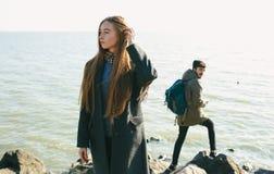 Красивые и стильные пары идя на скалистый пляж Пары одели в куртках, шляпах и ботинках Стоковое фото RF
