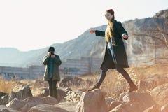 Красивые и стильные пары сфотографированы на скалистом пляже Пары одели в куртках, шляпах и ботинках Стоковая Фотография