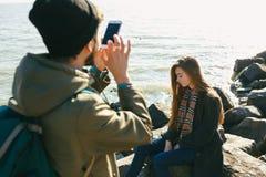 Красивые и стильные пары сфотографированы на скалистом пляже Пары одели в куртках, шляпах и ботинках Стоковые Фото