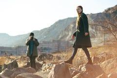 Красивые и стильные пары сфотографированы на скалистом пляже Пары одели в куртках, шляпах и ботинках Стоковое фото RF