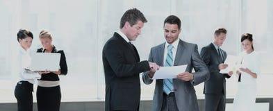 Красивые и уверенно бизнесмены работая на офисе стоковые изображения