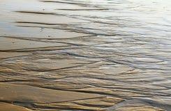 Красивые картины на золотом сияющем песке от сильного se стоковое изображение