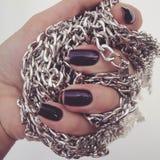 Красивые красные ногти и цепной конец вверх Красивые, хорошо выхоленные ногти с пурпурным маникюром и цепь в руке стоковое фото rf
