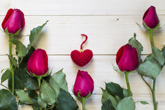 Красивые красные розы и красное сердце на деревянной предпосылке стоковые фото