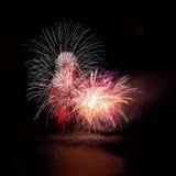 Красивые красочные фейерверки на воде отделывают поверхность с чистой черной предпосылкой Фестиваль потехи и международное состяз Стоковые Изображения RF