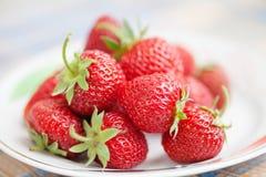Красивые клубники на плите Красные свежие ягоды с зелеными листьями Малая глубина фотографии поля, взгляда макроса Стоковая Фотография RF