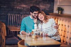 Красивые любящие пары сидя в кофе кафа выпивая и conversating Стоковое фото RF