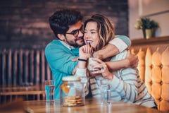 Красивые любящие пары сидя в кофе кафа выпивая и conversating Стоковые Изображения