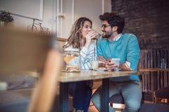 Красивые любящие пары сидя в кофе кафа выпивая Стоковые Изображения