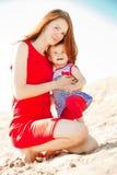 Красивые мама и младенец outdoors Счастливая семья играя на bea стоковое изображение