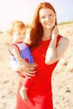 Красивые мама и младенец outdoors Счастливая семья играя на bea стоковое фото