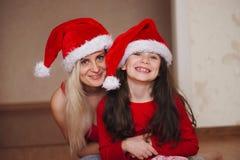 Красивые мать и дочь с шляпами santa Стоковые Изображения