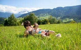 Красивые мать и дочь лежа на траве стоковые фотографии rf