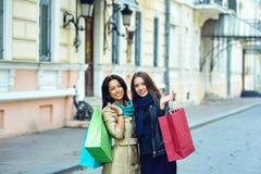 Красивые маленькие девочки имея потеху в городе делая покупки Стоковые Изображения RF