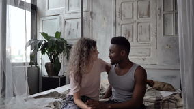 Красивые многонациональные пары в пижамах сидя на кровати и говорить Человек и женщина имеют переговор движение медленное видеоматериал