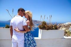 Красивые молодая женщина и человек в их летних каникулах идут на греческий остров Santorini Стоковое Изображение