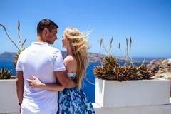 Красивые молодая женщина и человек в их летних каникулах идут на греческий остров Santorini Стоковое Изображение RF