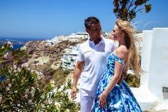 Красивые молодая женщина и человек в их летних каникулах идут на греческий остров Santorini Стоковое фото RF