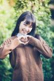 Красивые молодые азиатские женщины делая сердце формируют с руками и Sm стоковое фото