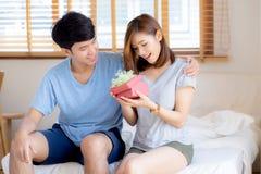 Красивые молодые азиатские пары в подарочной коробке сюрприза любов в спальне дома, годовщина семьи с наслаждаются и романтичный  стоковое фото