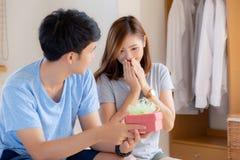 Красивые молодые азиатские пары в подарочной коробке сюрприза любов в спальне дома, годовщина семьи с наслаждаются и романтичный  стоковое изображение rf