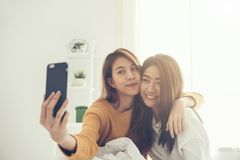 Красивые молодые азиатские пары женщин LGBT лесбосские счастливые сидя на объятии кровати и используя телефон принимая спальню se Стоковое фото RF