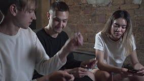 Красивые молодые друзья имея потеху на выравнивать игры игральной карты с превосходным настроением в современном клубе просторной акции видеоматериалы