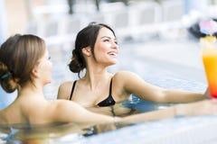 Красивые молодые женщины в бассейне Стоковая Фотография