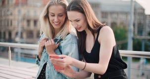 Красивые молодые женщины наблюдая фото на мобильном телефоне Стоковая Фотография