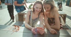 Красивые молодые женщины наблюдая фото на мобильном телефоне Стоковые Фото