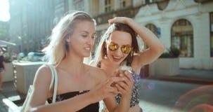 Красивые молодые женщины наблюдая фото на мобильном телефоне Стоковая Фотография RF