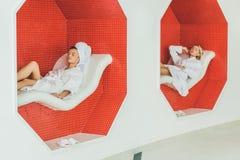 красивые молодые женщины ослабляя на софах Стоковая Фотография RF