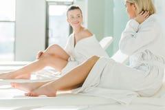 красивые молодые женщины ослабляя на sunbeds на спа-центре Стоковые Изображения RF