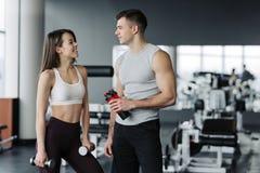 Красивые молодые люди спорт держат бутылки воды, смотрят один другого и усмехаются в спортзале стоковое фото rf