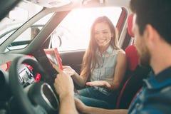 Красивые молодые пары стоя на дилерских полномочиях выбирая автомобиль для того чтобы купить стоковые изображения rf