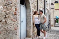 Красивые молодые пары стоя на каменной дороге около древних стен старого замка Стоковая Фотография