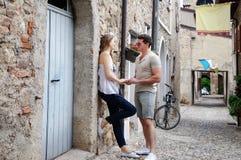 Красивые молодые пары стоя на каменной дороге около древних стен старого замка Стоковое Изображение