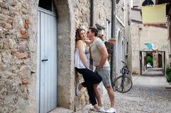 Красивые молодые пары стоя на каменной дороге около древних стен старого замка Стоковое Фото