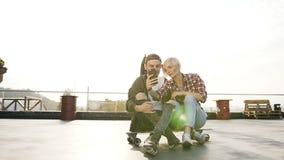 Красивые молодые пары хипстера сидят на скейтборде longboard на крыше современного здания и используют смартфон сток-видео