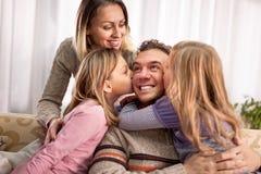 Красивые молодые родители и их милые маленькие дочери, huggin Стоковые Фотографии RF