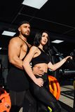 Красивые молодые sporty сексуальные человек и girll пар представляют положение в спортзале Стоковое фото RF