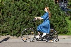 Красивые молодая женщина и велосипед года сбора винограда, лето Красная девушка волос ехать старый черный ретро велосипед снаружи стоковое фото